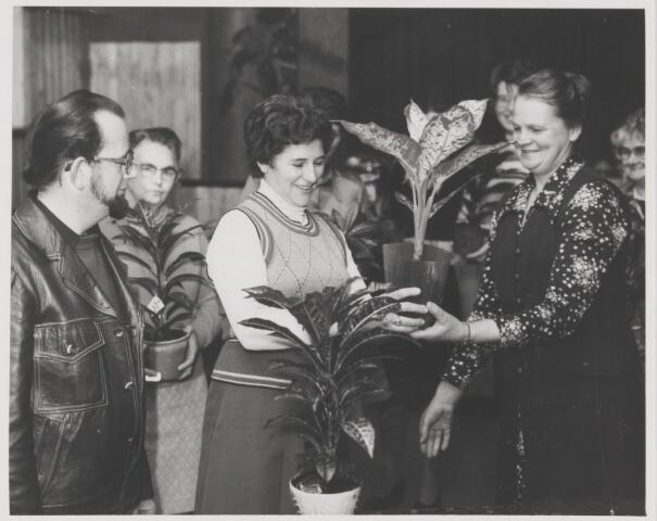 082183 - K.V.O. organiseert een kamerplantenwedstrijd. Op de foto in het midden de winnares Mevrouw Nuijten van Riel, links jurylid de heer Verharen (bloemist uit Dongen) en rechts voorzitter Mevrouw Klaassen