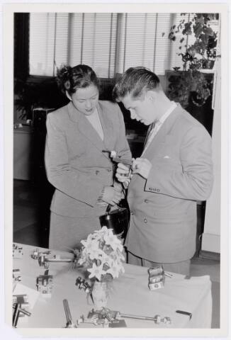 """038929 - Volt. Zuid. Tentoonstelling vakliedenopleiding Volt april/mei 1957. Locatie kantine Voltstraat. Deze kantine was de bovenverdieping van gebouw B. ( Zie het boekje """"Tussen gloeilamp en hoogspanningstrafo"""" bldz. 40.)  Dhr. Wagemakers met zijn toenmalige verloofde Fientje bekijken een z.g.n. gloeilampenklem. Dat was destijds een bekend proefstuk op de Philipsbedrijfsschool te Eindhoven. Misschien heeft hij het wel zelf gemaakt, want ook hij volgde deze opleiding."""