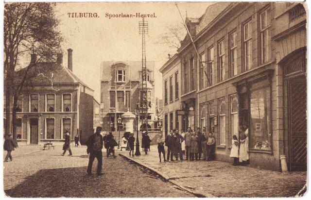 002122 - Spoorlaan richting Heuvel. Op de achtergrond links aan de Heuvel nr. 95i, vanaf 1930 nr. 103 het in aanbouw zijnde huis van Theodorus J.M.A. Kerstens. Kerstens was koopman in manufacturen en trouwde te Tilburg op 13.5.1907 met Louisa F.M.J. Swagemakers. Links hiervan een huis waarin o.a. keel-, neus- en oorarts P.J.M. van Iersel woonde. Tussen beide huizen een straatje dat liep naar de wollenstoffenfabriek van de firma Wed. J.B. de Beer. Nadat deze fabriek in 1928 verlaten was, vestigde Herman van der Waarden er de Burgerschouwburg. Rechts de straatwand aan de Spoorlaan. Op de hoek Heuvel/Spoorlaan het pand Heuvel nr. 6. Vervolgens de panden Spoorlaan N 245-246-247, vanaf 1910 Spoorlaan 2, 4 en 6. Rond 1910 woonde op nr. 2 schoenmaker Hendrikus van Gerwen. Hij verhuisde in 1911 naar de Heuvel. De nieuwe bewoner was sigarenfabrikant Johannes P.V. Roef. Pand nr. 6 werd  bewoond door boekdrukker Cornelis van Tilburg, geboren te Andel in 1869. Hij verhuisde in 1912 naar het pand Spoorlaan nr. 4. Hier brak in 1927 een staking uit in zijn bedrijf. De panden 4 en 6 zijn later afgebroken. Pand nr 6, links van de poort, werd rond 1960 verbouwd tot het moderne winkelpand van Max Wolff. Hij was radiohandelaar en verkocht volgens een grote lichtreclame op zijn gevel het merk 'Blaupunkt'.
