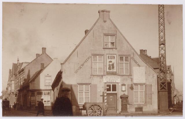 044923 - Het pand op de hoek Noordstraat (links) en Stationsstraat (rechts) vlak voor de sloop. Dit eeuwenoude Kempische woonhuis met de typische hoge voorgevel en lagere achtergevel, had rond 1900 het huisnummer Noordstraat M1076, even later veranderd in Noordstraat 104. In die tijd werd het pand bewoond door schoenfabrikant Jan Baptist Cornelis Dudar, geboren te Tilburg op 31 januari 1875 en getrouwd met Petronella Johanna Bossers. In 1916 verliet de familie Dudar dit pand om een schoenenzaak te beginnen in het pand Nieuwlandstraat 15. In het pand Noordstraat 104 was daarna tijdelijke de modezaak van de gezusters Heerkens gevestigd. Het pand is gesloopt vóór 1920. Voor het huis zien we een stootkar, een brievenbus van de P.T.T. en rechts een kooimast.