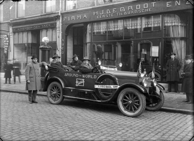 650513 - Schmidlin. J. de Groot, handelaar in auto's en rijwielen aan de Stationsstraat12. Deze Buick behoorde tot een reclamestunt van de Amerikaanse Buick-fabrieken. Vanuit Amerika werd deze auto van dealer naar dealer gereden en trok zo 'de aardbol om'. Links de schoenwinkel van H. Mensen-Denissen, Stationsstraat 10. Foto 1925.