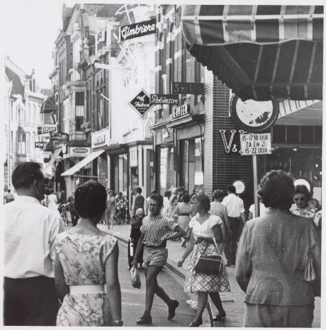 021613 - Winkelend publiek in de Heuvelstraat in 1959 ter hoogte van het pasverbouwde Vroom & Dreesmann, dat op 22 mei van dat jaar was heropend