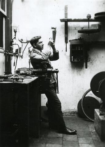 """200216 - Leo van Steensel (1894-1981) kwam op twaalfjarige leeftijd als leerling in de zaak van Frans Caarls eigenaar van een zaak in """"brillen, staalwaren en uurwerken"""" aan de Zomerstraat. In 1932 nam hij de zaak van Caarls over. Op de foto Van Steensel in de werkplaars van Caarls."""