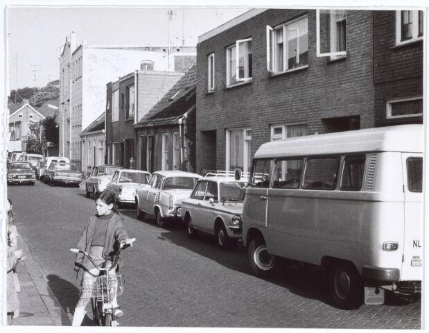 017261 - Capucijnenstraat in de richting van de Paterstraat. In e witte gevel van het gebouw rechts op de achtergrond is een beeld van St.-Aloysius aangebracht.  Daarachter een gedeelte van het voormalige Katholiek Militair Tehuis, thans buurthuis St.-Anna