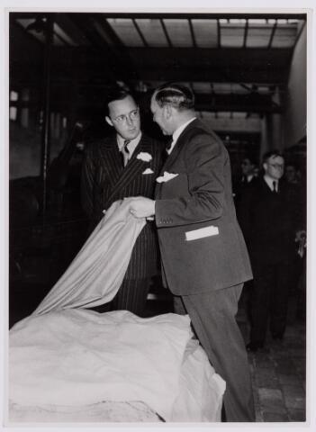 037675 - Textielindustrie. Vol belangstelling luistert prins Bernhard naar de uitleg van directeur Hein Enneking sr. van wollenstoffenfabriek H. F. C. Enneking aan de Goirkestraat dat hij op 13 november 1950 bezocht