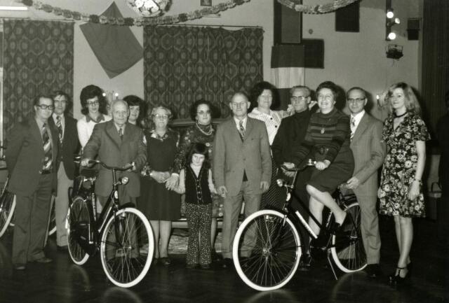 602251 - De prijswinnaars van een cctie van winkeliersvereniging Korvel Vooruit. De man met fiets links is Huub Janssen, rechts van hem zijn vrouw Anna. Het echtpaar Haans was  winnaar van de fiets rechts. Achter op de fiets Harrie Haans, voor hem zijn vrouw. Zij hadden een speelgoedwinkel aan het Burgemeester Van de Mortelplein. Vijfde van rechts Miet Baans-Meijers, winnares van een auto. Zij stond met een kousenkraam op de markt en had een textielzaak aan de Tafelbergstraat. Geheel  rechts Lenie Simons-Vermeer uit Hilvarenbeek. Ook zij won een fiets. De foto werd genomen in de dansschool van Boutkan aan de Korvelseweg.