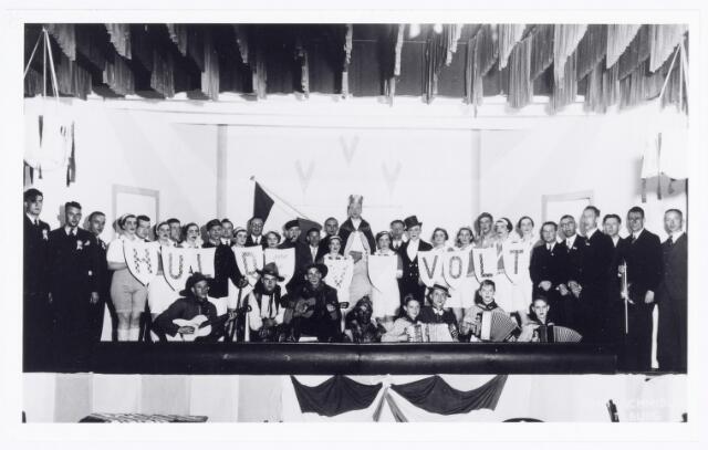 038793 - Volt. Sport en ontspanning. Voetbalvereniging. Zeer waarschijnlijk is dit een feestavond of revue van voetbalvereniging Volt (V.V.V.)  in 1935. Dat was het jaar van het 15 jarig bestaan. Dit was voor zover bekend de eerste sportvereniging bij Volt opgericht op 17 september 1920 door de heer Jan Vermeulen. In 1922 werd gymnastiekvereniging Volt door dezelfde Vermeulen opgericht die zich bij V.V.V. aansloot en zich in 1924 verzelfstandigde. Tot 1938 was dit een bedrijfsvoetbalclub spelend tegen elftallen van andere bedrijven.Dat ging zo goed dat men hogerop wilde. Om een licentie van de K.N.V.B. te krijgen werd V.V.V.  in 1938 opgeheven en opnieuw opgericht onder de naam V.V.Tac. De K.N.V.B. accepteerde de naam V.V.Volt niet (bedrijfsnaam?), of bestond V.V.V. Venlo toen al?  De staande heer 6e van rechts is Weijers, die vanaf de oprichting van V.V.Tac. in het bestuur zat en in 1963 zijn zilveren bestuursjubileum vierde. Hij werd toen gehuldigd met de K.N.V.B.speld. Staande 5e van rechts Dhr. Keulemans en 2e van rechts (met viool) Dhr. v.d. Hout. TAC heette na een fusie met BWB en Zouavia FC.Triborgh.(2003) In 2008 ging deze club failliet en werd voortgezet onder de naam Reeshof s.v.          V.V.V. speelde van 1920 tot 1937 aan de Niewe Goirleseweg ,dan in de Groenstraat tot 1941. Inmiddels Tac geheten, werd een terrein aan de Delmerweg in gebruik genomen en in 1962 werd weer verhuisd naar het Volt sportpark de Ezelvense Akkers in het Groenewoud. Tegen woordig (2014) voetbalt men in de Reeshof.