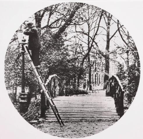 035124 - Een lantaarnpoetser uit 1930 die in het Wilhelminapark een lantaarn nabij het bruggetje aan het poetsen is