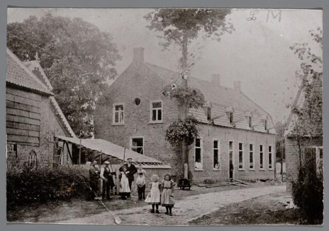"""065562 - De heer L Moreau liet omstreeks 1900 naast zijn looierij een woning bouwen aan de Waterstraat; thans is hier gevestigd het cafe """"De Bonten Os """"; v.l.n.r. Jan Ermes en een andere looiersknecht; Louise Verheijen en achter haar een looiersknecht; verder Louis, Jef, Louise en Amalie Moreau"""