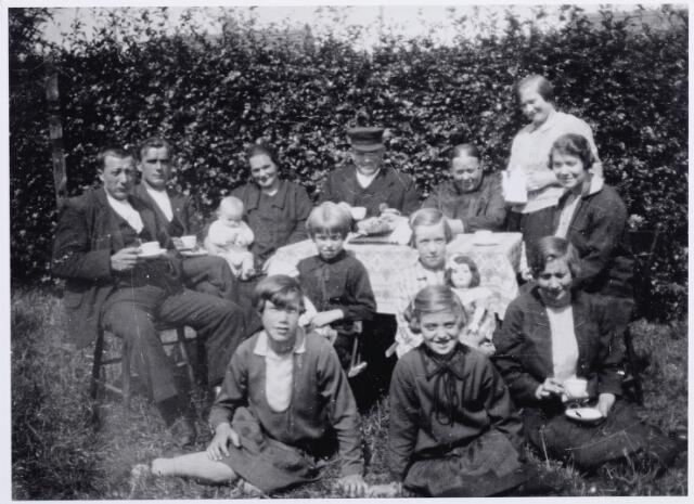 046187 - Foto genomen in de tuin van de familie Van Wezel-Swanen in de zomer van 1929. Achter de tafel v.l.n.r. Jan van Wezel, Antoon Bruers, Miet Bruers-van Wezel met zoon Jan, Piet van Wezel, zijn vrouw Mie Swanen, staande, Pietje van Wezel en Anna van Wezel. Rechts op de voorgrond, met kopje in de hand, To van Wezel. Links van haar Cor Swanen, het pleegkind van Piet van Wezel. De andere drie meisjes kwamen uit Rijen en waren bij Piet op vakantie.