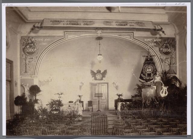 """052408 - Muziekleven. Interieur van de concertzaal van de Koninklijke Liedertafel Souvenir des Montagnards in 1904. Op het decor ' Oefening baart Kunst', 'Kunst baert Roem'.  Het betreft hier 't door Liedertafel """"St.Cecilia"""" en harmonie """"Tilburgsche Capelle"""" aan dirigent Leo Swagemakers ( 1859 -1904 ) aangeboden concert bij zijn afscheid als DIRIGENT VANDE SOUVENIR ! Hij nam zelf ontslag na veel geruzie, dus van Souvenir had hij bij zijn afscheid niet veel te verwachten.  Wie de twee gezelschappen heeft uitgenodigd is niet bekend. Op 't podium staat zijn portret; dit hangt nog altijd in de societeit van de Souvenir. De Nw.Tilb.Courant besteedde veel aandacht aan dit curieus gebeuren !"""