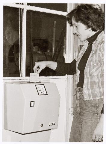 """039410 - Volt, Noord. Hulpafdelingen, Administratie. De nieuwe tikklok voor keuzewerktijden. Deze foto is gemaakt n.a.v. de invoering van de z.g.n. """"Keuzewerktijden"""" bij Volt. In 1976 startte men met een proef in enkele afdelingen.Tot 1979 werd de keuzewerktijd stapsgewijs ingevoerd in de overige afdelingen."""