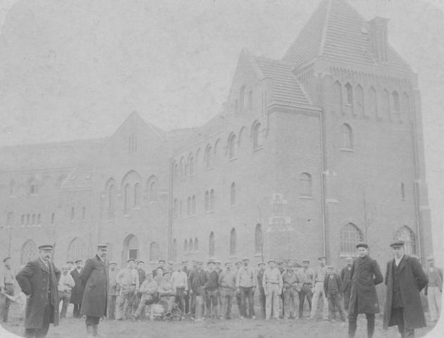 """105208 - Groepsfoto met bouwvakkers voor het kloostergebouw.  De abdij werd gebouwd tussen 1906 en 1909.  Bij deze foto staat achterop geschreven: """"Het huis is voltooid (eind 1909). Het glas is in de ramen. 46 Arbeiders werkten aan de bouw. (Kastanjebomen waren geplant in Dec. 1906)"""". Kloosters"""