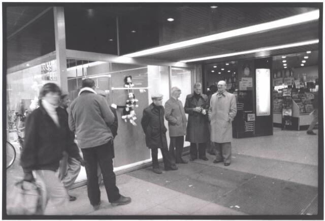 021938 - Buurtende mensen bij de ingang van Vroom & Dreesmann in de Heuvelstraat in november 1981
