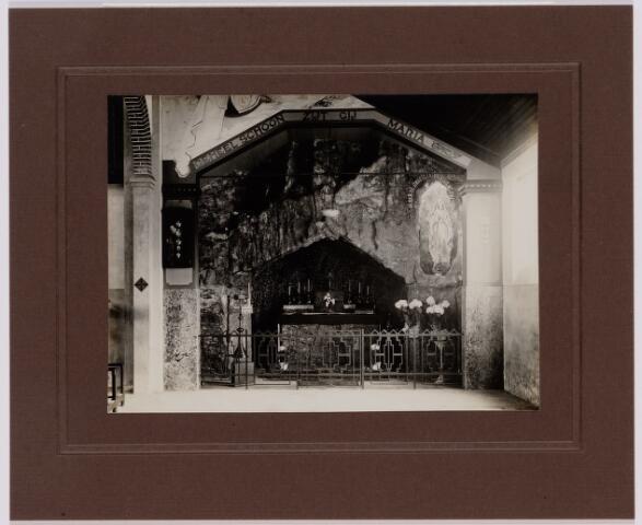049463 - Lourdesgrot in de oude noodkerk van O.L.V. van Lourdes (Koningshoeven). De kerk was gevestigd in een voormalig fabriekspand. De noodkerk werd in gebruik genomen in 1921. In 1965 werd een nieuwe kerk in gebruik genomen.