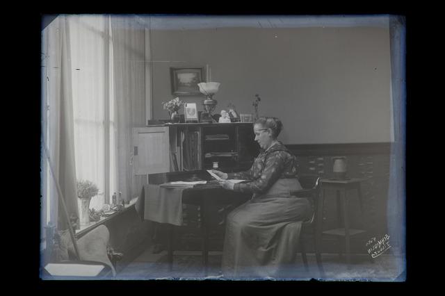 654825 - Interieur. [Johanna Schmidlin] poseert in het atelier aan de Gasthuisstraat. Zij zit aan een bureau en leest een brief.  (zie ook fotonr. 654804)