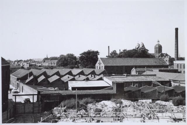025943 - Fabriek van Van Riel aan de Zomerstraat, thans Louis Bouwmeesterplein, eind september 1959. Op de achtergrond rechts de St. Annakerk en op de voorgrond de bouw van de Stadsschouwburg