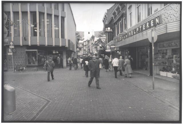 021912 - Begin van de Heuvelstraat, gezien van de Heuvel. Links, op de hoek met de Juliana van Stolbergstraat, de modezaak van Van de Brekel. Op de andere hoek electronicahandel Nico van Helfteren, gevestigd in een van de twee voormalige filialen van De Gruyter in de Heuvelstraat