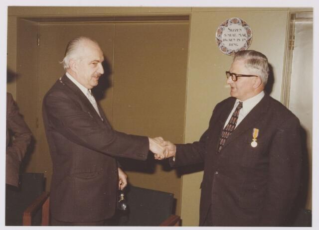081343 - Uitreiking Koninklijke onderscheiding in goud aan P.C. van Poppel (geb. 29-12-1915) door burgemeester P.G. Ballings.
