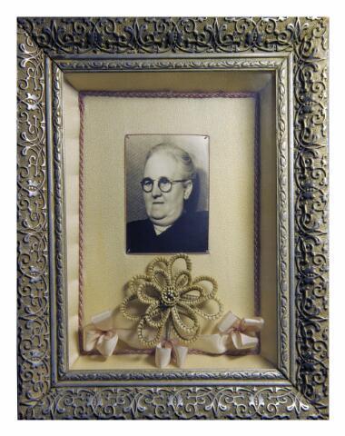 604546 - Vorselaars-de Jong, haarwerkschilderij. Foto met gevlochten haar van de overledene.  De afgebeelde dame is Anna Joanna Norberta Vorselaars-de Jong. Zij werd op 29 oktober 1884 in Tilburg geboren als dochter van Cornelis Johannes de Jong en Francisca Gertruda van der Steen.  Op 28 oktober 1913 huwde zij te Tilburg met machinist Henricus Joannes Joseph Vorselaars. Anna overleed in haar geboorteplaats op 1 februari 1953. Na haar overlijden werden afgeknipte haren en een foto samengesteld tot een haarwerkschilderij ter herinnering aan de overledene. Dergelijke haarwerkschilderijen en ook sieraden werden meestal gemaakt naar aanleiding van het overlijden van een dierbare. Dit was gebruikelijk in de 19e eeuw, maar kwam zeker in het begin van de 20e eeuw nog veel voor. Het portret werd geschonken door de zonen van Zus Vorselaars Hamers