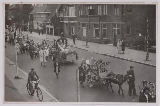 042858 - Koninginnedag. Een stoet buurtbewoners paradeert op de Nieuwe Bosscheweg ter gelegenheid van de verjaardag van koningin Wilhelmina op 31 augustus 1945