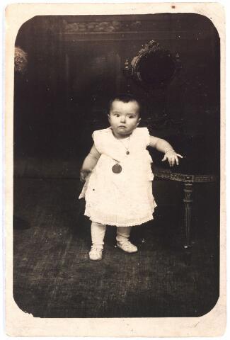 007785 - In de Veemarktstraat nummer 38 werd 21 maart 1925 de 70.000e inwoonster van Tilburg geboren, M.A. de Rooij. In de krant verscheen later het volgende bericht: 'Door Tilburg Vooruit en eenige ambtenaren werd hedenavond aan de ouders de van de 70-duizendste inwoonster van Tilburg een herinneringsmedaille aangeboden met een spaarbankboekje waarop een flinke duit is geplaatst. Alsnog werd de toezegging gedaan dat van vader, moeder en kind een foto zal worden gemaakt'. Deze foto werd uit dankbaarheid door de ouders aan het bestuur van Tilburg Vooruit gestuurd. Op de foto draagt het meisje de herinneringsmedaille.