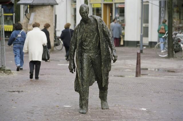 """TLB023000229_003 - Standbeeld """"De lopende man"""" op de markt tussen Heuvelstraat en Schouwburgring  en is gemaakt door Peter Erftemeijer in 1990. Samen met het zitbankje van Dora Dolz en de Staande hartvorm van Peter van den Berk was dit beeld speciaal gemaakt ter aankleding van de winkelgalerij 'Schouwburgpromenade' bij de opening. Maar er was kritiek: """"De uitgebeelde figuur kun je niet bepaald rekenen tot de groep van koopkrachtige consumenten die de winkelier graag zijn zaak ziet binnenkomen. Een plaatsje in de overdekte winkelstraat was dan ook niet voor hem weggelegd""""."""
