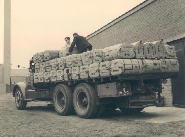 650897 - Textielweverij Mutsaers & Van Poppel, Tilburg. Balen textiel (kamgaren stoffen)  werden via de vrachtwagens vervoerd naar de trein. Deze open vrachtwagen staat op het terrein van de firma Mutsaers & Van Poppel.