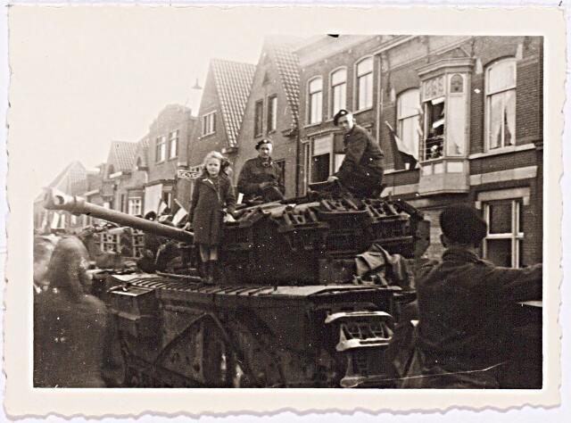 012245 - Tweede Wereldoorlog. Bevrijding. Een meisje poseert op een tank, die gepaarkeerd staat op de Korvelseweg,  naast Britse soldaten