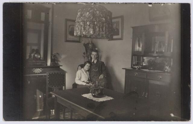 049052 - Adrianus Jozef (Janus) van de Ven, directeur van melkinrichting de Hoop aan de Sophiastraat 18a met zijn vrouw Anna Maria (Antje) Louwers. Zij trouwden te Oirschot in 1924, het jaar waarin deze foto werd genomen. Het huis was de bovenwoning van de melkinrichting. Van de Ven werd geboren te Oirschot op 10 december 1897 en overleed aldaar op 21 juni 1981. Zijn vrouw werd geboren te Oirschot op 16 december 1901. Zij overleed te Tilburg  op 2 december 1965. De foto toont een interieur uit de jaren twintig van de 20e eeuw met een buffetkast, een kolenhaard, een spiegel boven de schouw en achter het echtpaar een H. Hartbeeld. Verder aan de wand de foto's van de ouders van Janus van de Ven: Adrianus van de Ven en Emerentia Beekmans uit Oirschot.