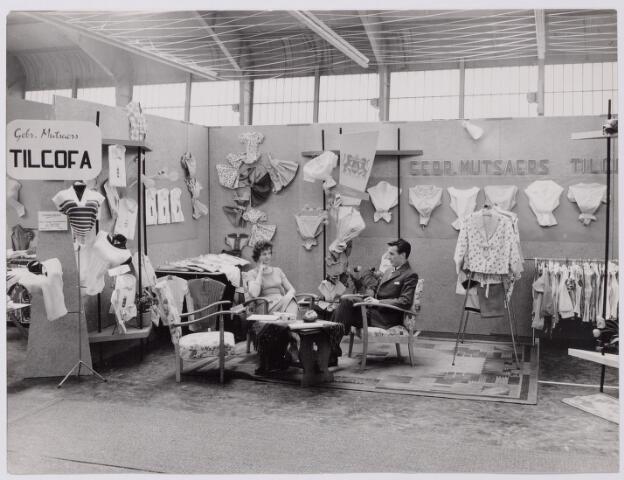 043974 - Stand van confectiefabriek Gebr. Mutsaers (Tilcafo) uit Tilburg op een beurs in Eindhoven.