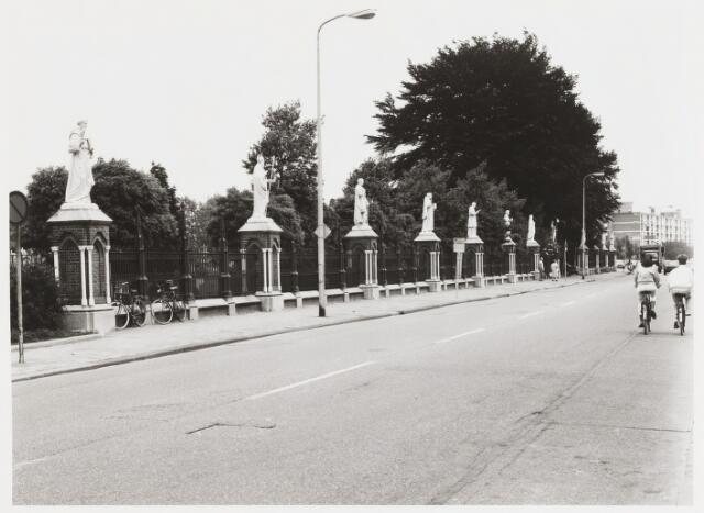 """067854 - HEKWERK MET HEILIGENBEELDEN rond kerkhof Bredaseweg. Hekwerk: A. van der Schoot en L. Petit, Tilburg. Beelden (van gietijzer): o.a. ijzergieterij Capitain & Salin (Frankrijk). Pastoor Van der Lee vatte in 1887 het plan op om het kerkhof van zijn parochie ('t Heike) van een waardige afsluiting te voorzien. Langs de Bredaseweg verrees over een lengte van 160 meter een neogotisch hekwerk met bakstenen pijlers. Het was aan de meer welgestelde parochianen er voor te zorgen dat op elke pijler een heiligenbeeld zou komen te staan. Het eerste beeld (Joannes de Doper) werd in 1892 geschonken door de erven van kerkregent Brouwers. In 1903 was de beeldengalerij compleet; 20 beelden, die oorspronkelijk allen langs de Bredaseweg stonden. Vanwege de aanleg van de Noordhoekring werd een gedeelte van het hekwerk afgebroken, en werden ook beelden langs de Noordhoekring geplaats. Begin jaren zeventig dreigde ook de rest te moeten wijken voor de verbreding van de Bredaseweg. Dankzij het actiecomité """"Heiligen gaan niet naar de hel"""", onder aanvoering van de historicus prof. dr. H.F.J.M. van den Eerenbeemt, ging het plan niet door. Het protest leidde zelfs tot restauratie van het hek en de beelden. De heiligen die plaats hadden moeten maken voor de Noordhoekring, kregen een nieuwe opstelling langs die weg. De galerij bestaat uit de volgende beelden (van west naar oost, en aansluitend langs de Noordhoekring van zuid naar noord): St. Antonius van Padua, St. Nicolaas, David, St. Franciscus van Assisië, St. Carolus Borromeus, St. Petrus, Maria als """"Mater Dolorosa"""", de Verrezen Christus, twee apocalyptische engelen, St. Johannes de Doper, St. Jozef, St. Barbara, St. Franciscus van Sales, de aartsengel Michaël, St. Catharina van Alexandrië, St. Agnes van Monte Pulciano, St. Cecilia en St. Henricus. (Foto uit 1985) Trefwoorden: Kunst,openbare ruimte."""