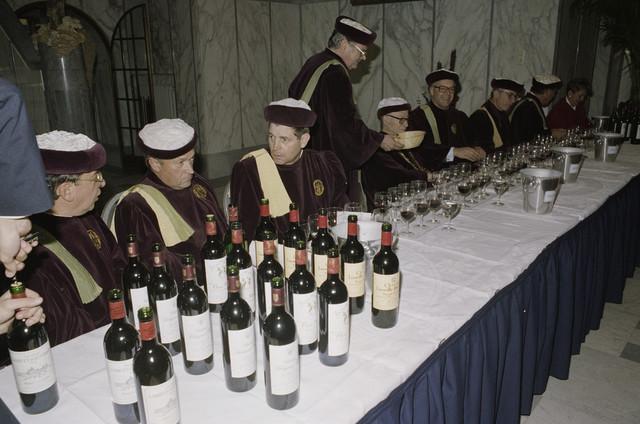 """TLB023000399_003 - Ter gelegenheid van Tilburg Wijnstad is er een wijnproeverij van Bordeaux wijnen in het Paleis Raadhuis, georganiseerd door wijnbroederschap """"Commanderie du Bontemps de Médoc, des Graves, de Sauternes et de Barsac"""".  Dit is het oudste en grootste broederschap van Frankrijk in het Departement Gironde en het Arrondissement Bordeaux. Bij deze gelegenheid werd ook de keuze gemaakt voor de nieuwe """"Tilburg Wijnstad Wijn"""".  Tilburg Wijnstad organiseert  jaarlijks een evenement dat bestaat uit een 'ommegang' van wijnbroederschappen, een oogstdankmis in de Heikese kerk en een wijnstraatje. De Emmapassage is jaren hiervoor gebruikt.  Het evenement is gebaseerd op het feit dat in Tilburg vanouds grote wijnfirma's gevestigd waren, zoals Wijnkopers Verbunt en André Kerstens. Aan het einde van de jaren zestig van de vorige eeuw werd de naam Tilburg Wijnstad al bedacht om Tilburg op een andere manier onder de aandacht te brengen dan als Textielstad."""