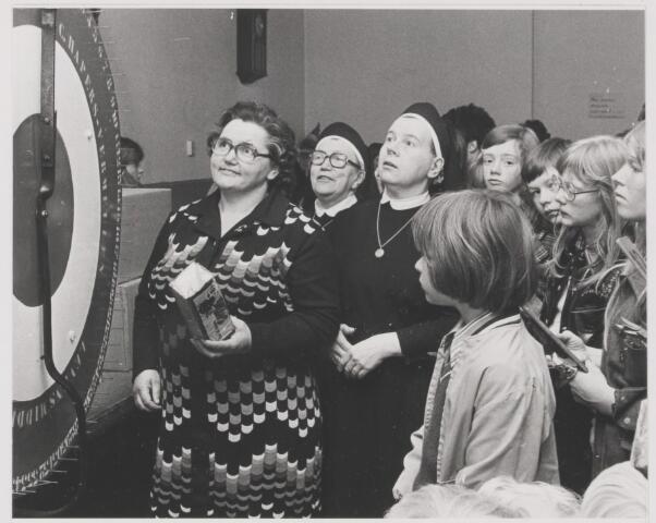 082016 - Gilze. Tentoonstelling en fancy-fair van de missie-naaikring. Nonnen en kinderen kijken gespannen naar het Rad van Avontuur voor de verloting van een peperkoek
