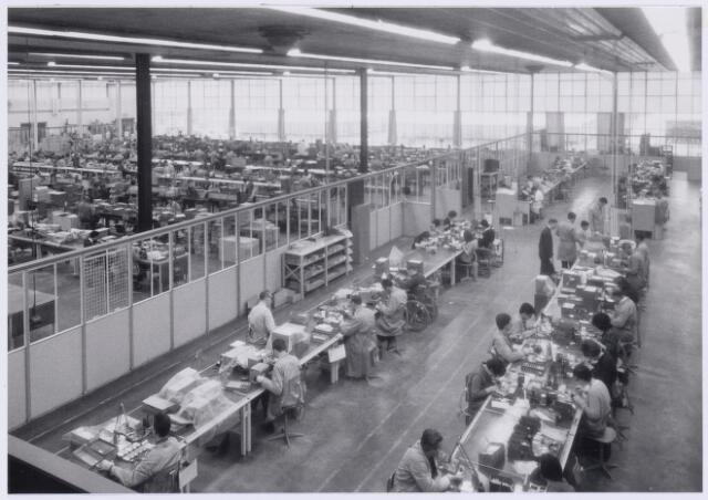 038995 - Volt. Zuid. Fabricage. Productie. Condensatoren. Hoewel Volt in noord reeds activiteiten ontplooide werd in zuid nog een nieuwe fabricagehal gebouwd die gereed kwam in 1959, hal Z genaamd. ( Tussen gloeilamp en hoogspanningstrafo bldz. 40 )  Deze was bedoeld voor de afd. condensatoren doch deed eerst dienst als jubileumhal i.v.m. het 50 jarig bestaan van Volt. (gevierd op zaterdag 26 september 1959 ) Begin 1960 werd de hal bevolkt met personeel van de afd. condensatoren. De z.g.n. variabele afstemcondensatoren voor radio met luchtspleten tussen rotoren en statoren werden toen langzamerhand vervangen door condensatoren met kunststof folie als diëlectricum. Op de foto is rechts de productie van foliecondensatoren te zien. Dat is nog handmatig en zal ongeveer in 1963 zijn. Later werd deze hal ook bevolkt door de afd. tuners of kanalenkiezers ( 1970-1975 ) en vanaf 1975 t/m 1979 werden er ook deflectie-units gefabriceerd. De hoge glaswand in de westgevel ( zie achter op de foto ) deed de temperatuur in de hal `s zomers zo hoog oplopen dat rond 1973 werd besloten een groot deel te isoleren. Dat meerdere afdelingen de hal konden gebruiken had alles te maken met de steeds verdergaande automatisering van de condensatorproductie waarbij steeds minder personeel nodig was. Van de  staande mannen rechts is de middelste Jos Vialle en in dezelfde rij vooraan Bert van de Pas. Aan de linkse voorste band zittend aan de linkerkant Noud van Trier een onderbaas.