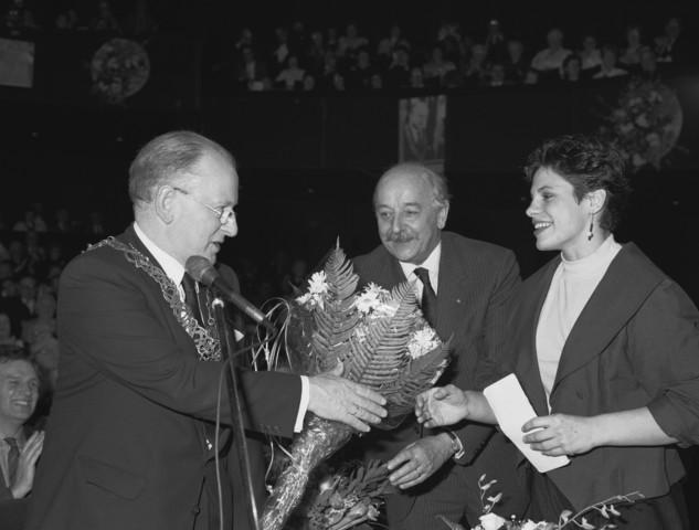 TLB023002737_001 - Bestuur. Burgemeester Henk Letschert neemt bloemen in ontvangst van o.a. judoka Irene de Kok bij zijn afscheid in maart 1988.