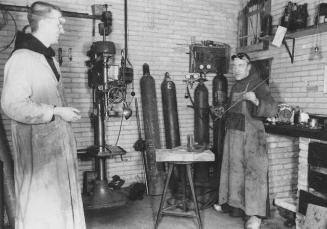 105280 - Monnikenleven Werkzaamheden in de smederij van de Sint Paulusabdij, met rechts broeder Ansfridus, rond 1940. Kloosters