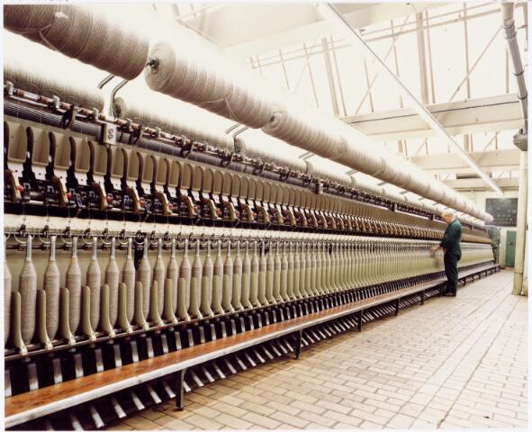 037962 - Textiel. Ringspinmachine bij C. Mommers. Door het draaien van de spillen werd het voorgaren tot een stevige draad gedraaid. Al naar gelang de dikte van die draad werd de toevoer geregeld: hoe dikker de draad, hoe sneller de toevoer