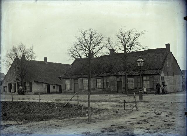 650574 - Schmidlin.Een boerderij en vervallen wevershuisjes aan de Oerlesestraat, hoek Veestraat, Man, vrouw en twee kinderen poseren voor het huis; omstreeks 1925.