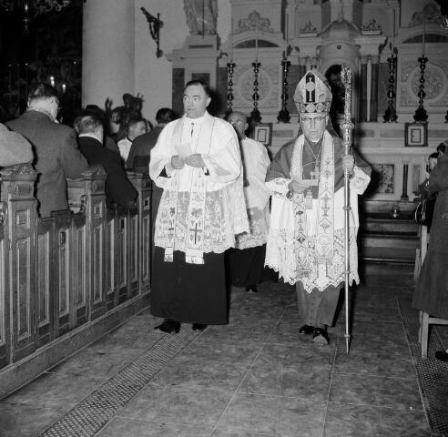 050559 - Installatie: pastoor van het Heike Wilhelmus Marinus  Bekkers (1908-1966). Wilhelmus Marinus Bekkers - wiens roepnaam Willem, Rinus of Rinie was - werd op 20 april 1908 te Sint-Oedenrode geboren als zoon van de landbouwer Willem Bekkers en Barbara Krol. Op 9 mei 1966 overleed hij op 58-jarige leeftijd  aan de gevolgen van een hersentumor. Zijn uitvaart in de Sint-Janskathedraal te 's-Hertogenbosch en de begrafenis op het kerkhof van de Sint-Martinusparochie in zijn geboortedorp groeiden uit tot een nationale gebeurtenis.