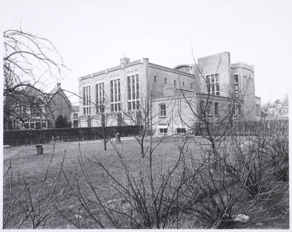 018550 - Tuin achter de kerk van O.L. Vrouw van Altijddurende Bijstand aan de Gasthuisring. Het was een ontwerp van ir. J.C. van Buytenen. Van 1955 tot 1974 als het als kerk in gebruik. In 1983 werd het verbouwd tot kantorencomplex. Het gebouw links werd eind 1981 gesloopt.