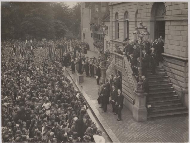 042633 - Muzikale hulde aan het gemeentebestuur in september 1923 bij het stadhuis ter gelegenheid van het 25-jarig regeringsjubileum van koningin Wilhelmina. Het Tilburgse publiek is in grote getale toegestroomd om onder leiding van A. de Groot (op het bankje staande), dirigent van de NK Harmonie, het Wilhelmus mee te zingen
