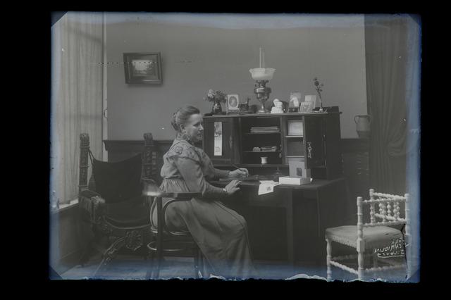 655000 - Interieur. Portret. Foto van een schrijvende vrouw aan een bureautje. Privé collectie Schmidlin, wrs rond 1917