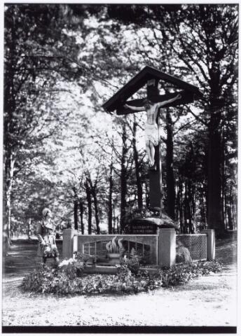 """049827 - Dierentuin. Foto uit ´Je Taalboek´ van frater Victor van Nispen.Wegkruis aan de Bredaseweg. Het kruis stond eerder aan de Delmerweg op de hoek van de Bredaseweg """"eenzaam op een stenen blok"""". Daar moest het kruis al snel verdwijnen omdat het omringende terrein een bouwbestemming kreeg. Het kruis werd opgeslagen op een boerenerf , totdat de familie Kerstens-Bogaers grond beschikbaar stelde """"bij de ingang van de holle weg tegenover het dierenpark"""". Het kruis werd opnieuw gepolychromeerd en herplaats met een hekwerk en op een voetstuk met een marmeren plaat waarop de tekst: """"Sla een blik op mij, en ga in vree voorbij"""". Op zondag 8 september 1935 trok een processie, bestaande uit 69 verschillende groepen naar het kruis, dat deken J.F.M. Sanders inzegende, gevolgd door een preek, het zingen van het """"kruislied"""", een spreekkoor van """"de Jonge Wacht"""" en een defilé van de 69 groepen. Men sprak over """"een smeekstoet die zijn weerga niet vond"""". Na vijf jaar stond het kruis echter weer in de weg voor de aanleg van de grote weg richting Eindhoven, die juist op dit punt begon. Tot overmaat van ramp brak bovendien de oorlog uit en maakten Franse troepen juist bij het kruis een verdedigingslinie, maar """"hoe kogels en granaten ook rondvlogen, het kruis kreeg geen letsel"""". Enkele maanden later is het kruis verplaatst naar de Warande, waar de eigenares plaats bood aan de zijde van de Bredaseweg, ook voor het bijplaatsen van een inmiddels geschonken beeld, om er een monumentaal geheel van te maken.  Het comité """"Tilburgs wegkruis"""", bestaande uit P. Verbraak, C. Smits en G. van Delft, zorgde in 1952 voor electrische verlichting bij het kruis, een reden om op 20 juli 1952 opnieuw een bid- en smeektocht te organiseren, waaraan 10.000 Tilburgers deelnamen en pater Generosus van de capucijnen een preek hield, waarin het zei dat er Christus niet langs de weg geplaatst zou moeten worden, maar midden op ieders levensweg zou moeten staan."""