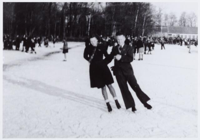 053864 - Sport. Schaatsen. Schaatsen op de ijsbaan Koningshoeven met op de voorgrond Annette van Berkel.   De schaatsbaan lag tussen Huize Dennenhaghe en de wollenstoffenfabriek van de firma Verschuuren - Piron aan de Koningshoeven.