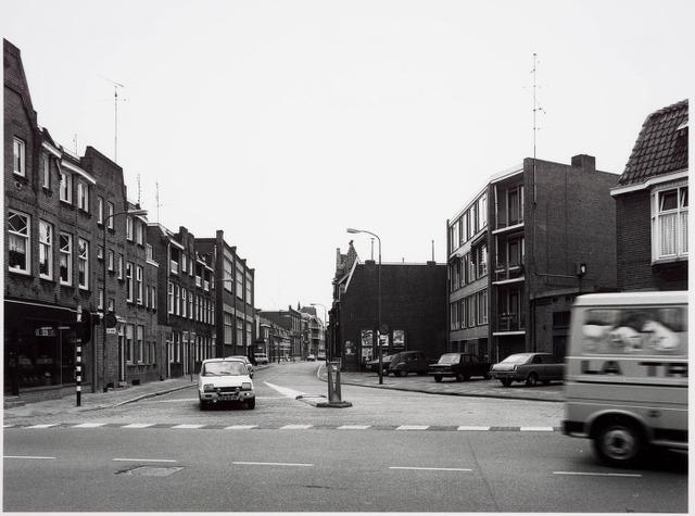 034106 - De Voltstraat gezien vanaf het voorplein van de kerk van Broekhoven I aan de Broekhovenseweg in westelijke richting. De huizen links zijn gebouwd in de stijl van de Amsterdamse school. Het daarachter liggende gebouw was van Volt. De bovenste verdieping hiervan deed lange tijd dienst als kantine en gymnastiekzaal voor de sportver. Volt. Op de begane grond werden gedurende lange tijd lampen, radiobuizen en speciale condensatoren gemaakt. Ook was hier ongeveer van 1963 tot 1975 de ontwerpgroep condensatoren gehuisvest incl. de tekenkamer en proevenwerkplaats. Direct achter dit gebouw was tot 1961 de hoofdingang van Volt. Direkt na de woonhuizen links het oude hoofdkantoor. De foto is van juni 1982.