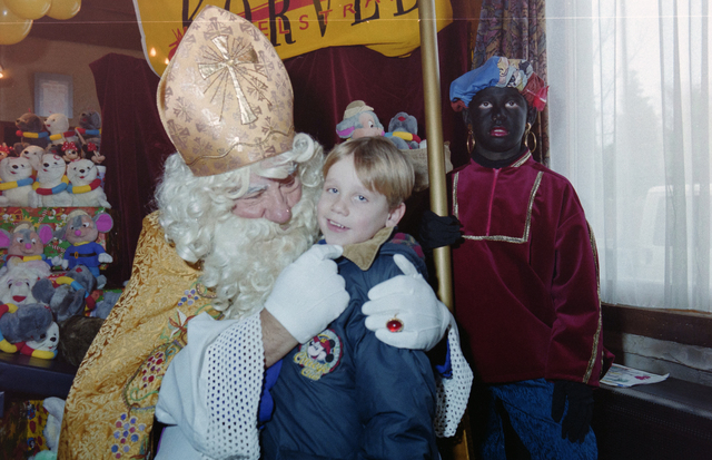 1237_001_003_017 - Feest. Korvel Winkelstraat. Sint Nicolaasviering. Een kind poseert met Sinterklaas en Zwarte Piet tijdens een Sinterklaasfeest georganiseerd door winkeliersvereniging Korvel Vooruit op 27 november 1999.
