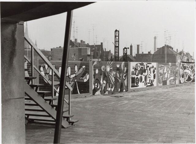 032591 - Stadsvernieuwing. De schuttingen rond de nieuwbouw aan het Stadhuisplein  werden door diverse leerlingen van scholen beschilderd; op de voorgrond de noodingang aan de achterzijde van het Paleis Raadhuis