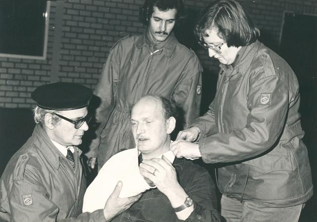651485 - VOLT, Tilburg.Noord.Vermoedelijk rond 1980. B.Z.B., A.H.V., afkortingen voor de beschermings- en hulpverleningsgroepen bij Volt. Hier een E.H.B.O. oefening. Links Gerrit Damen en rechts  Lenie Mols.