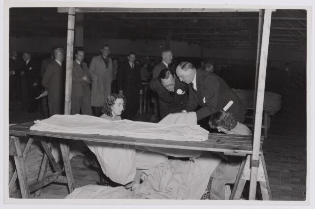 037660 - Textielindustrie. Prins Bernhard kijkt vol belangstelling naar het werk van twee stopsters bij H. F. C. Enneking tijdens diens bezoek aan de fabriek op 13 november 1950